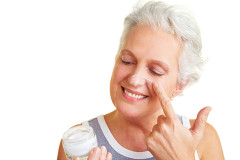 older woman with jar of face cream