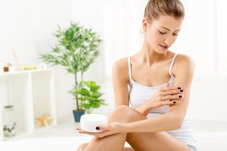 39336254 – beautiful young woman applying body lotion.