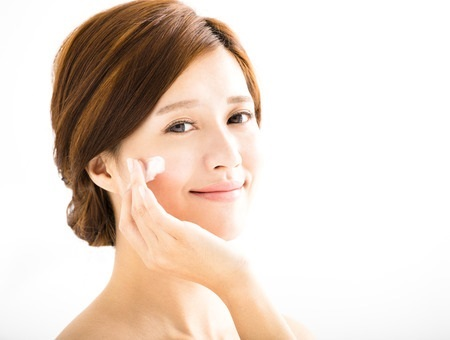 49241551 – smiling woman applying cream lotion on face