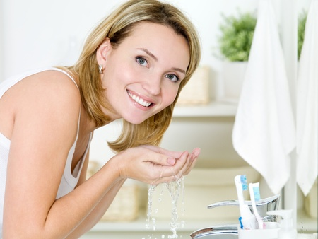 10668411 – young happy woman washing face with water standing in bathroom