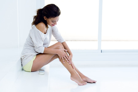 41802200 – body care. woman applying cream on legs