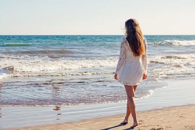 woman in white on beach pixabay 2